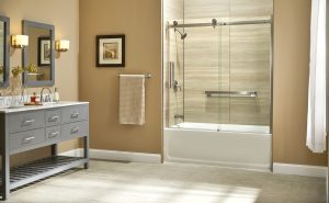 Soaker tub in beige bathroom with sliding shower door and stainless finishes