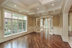 A large living room with glass French interior doors and a large set of windows with grille patterns.